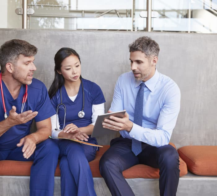 Healthcare workers in discussion using a tablet computer