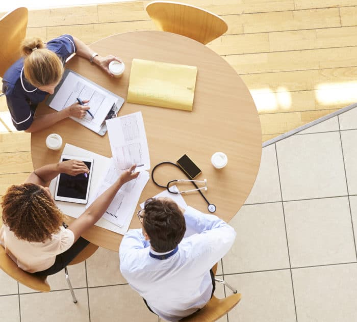 Three senior healthcare workers in a meeting, overhead view